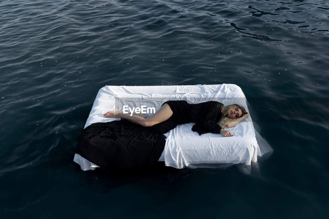 High angle view of young woman sleeping on bed floating in lake