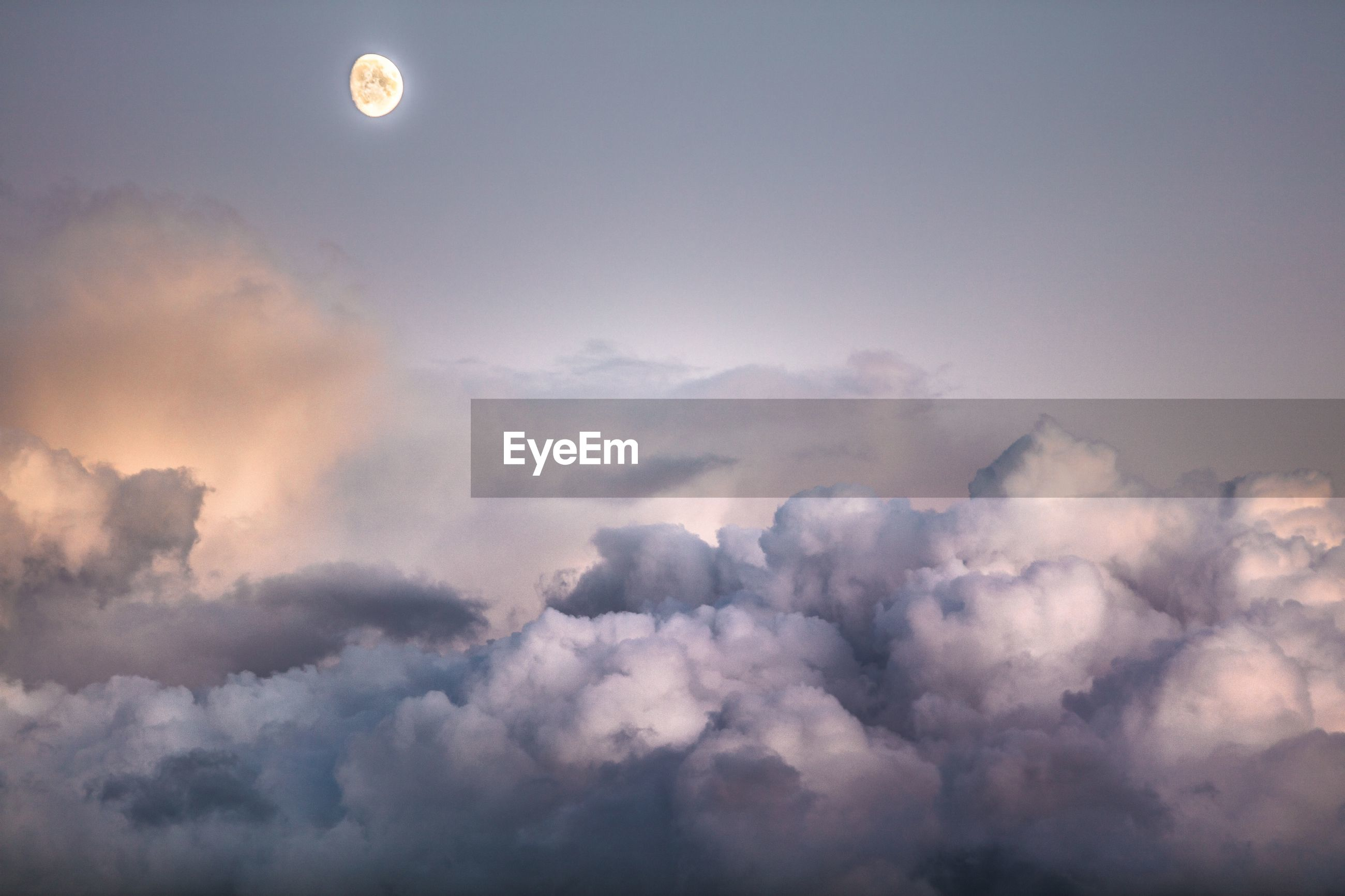 Low angle view of moon in sky during sunset