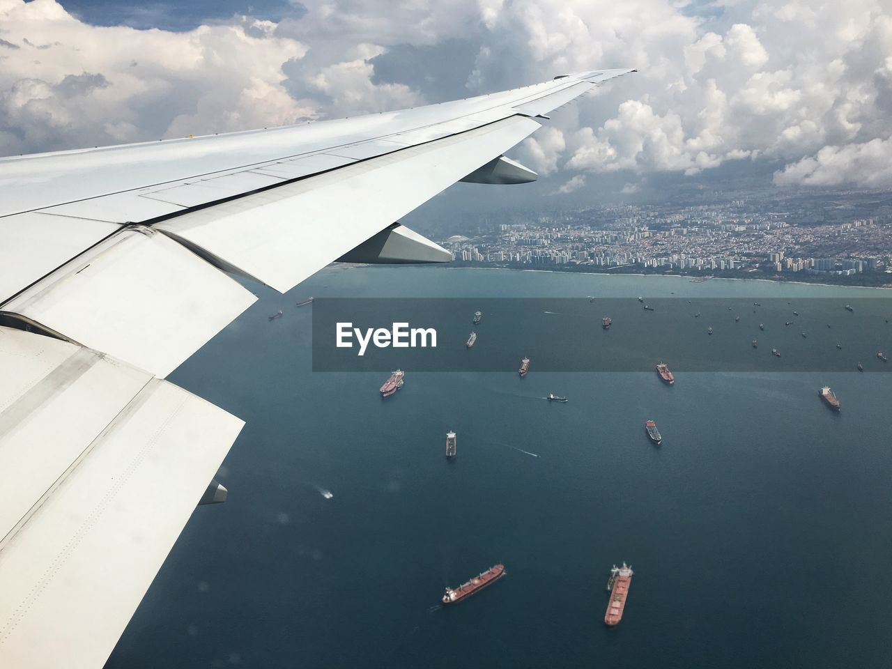 Airplane Flying Above Sea Against Cloudy Sky