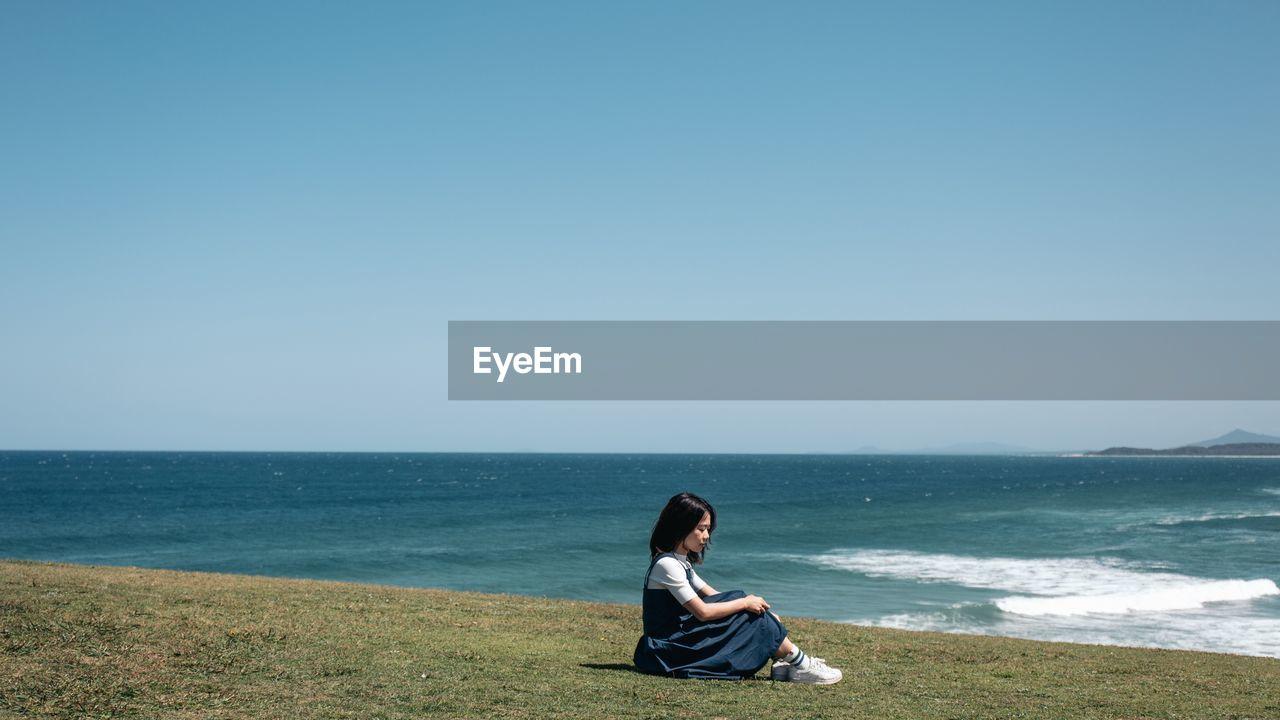 Woman sitting at beach against clear sky