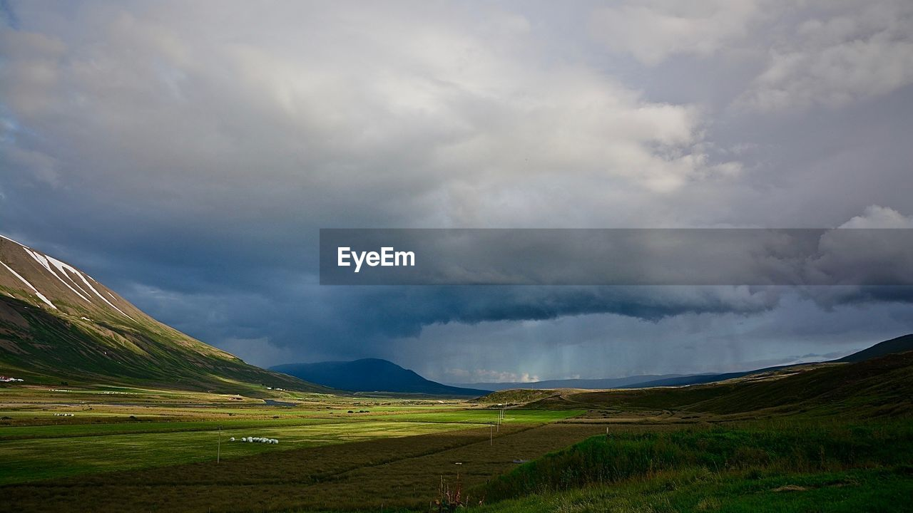 Scenic view of landscape against cloudy sky during monsoon