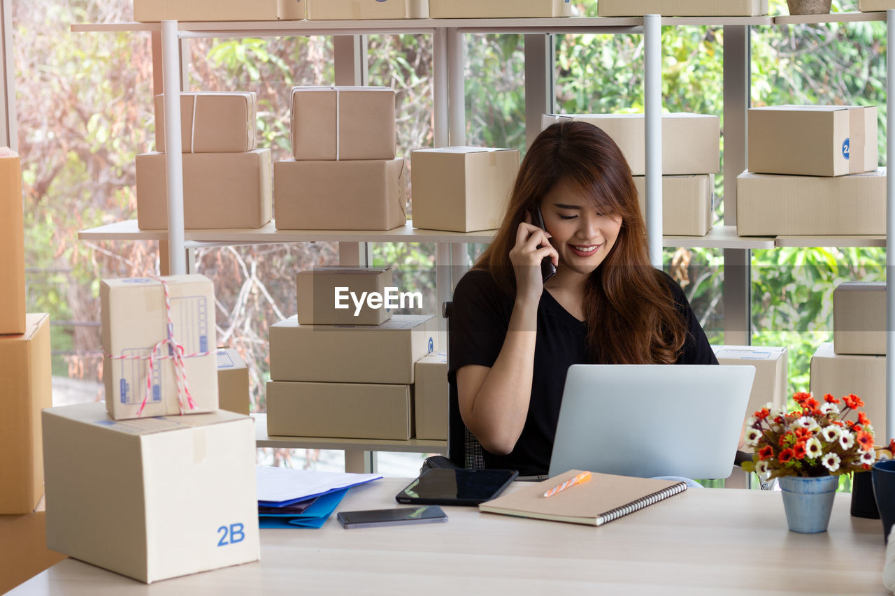 Woman talking over smart phone while sitting against boxes in office