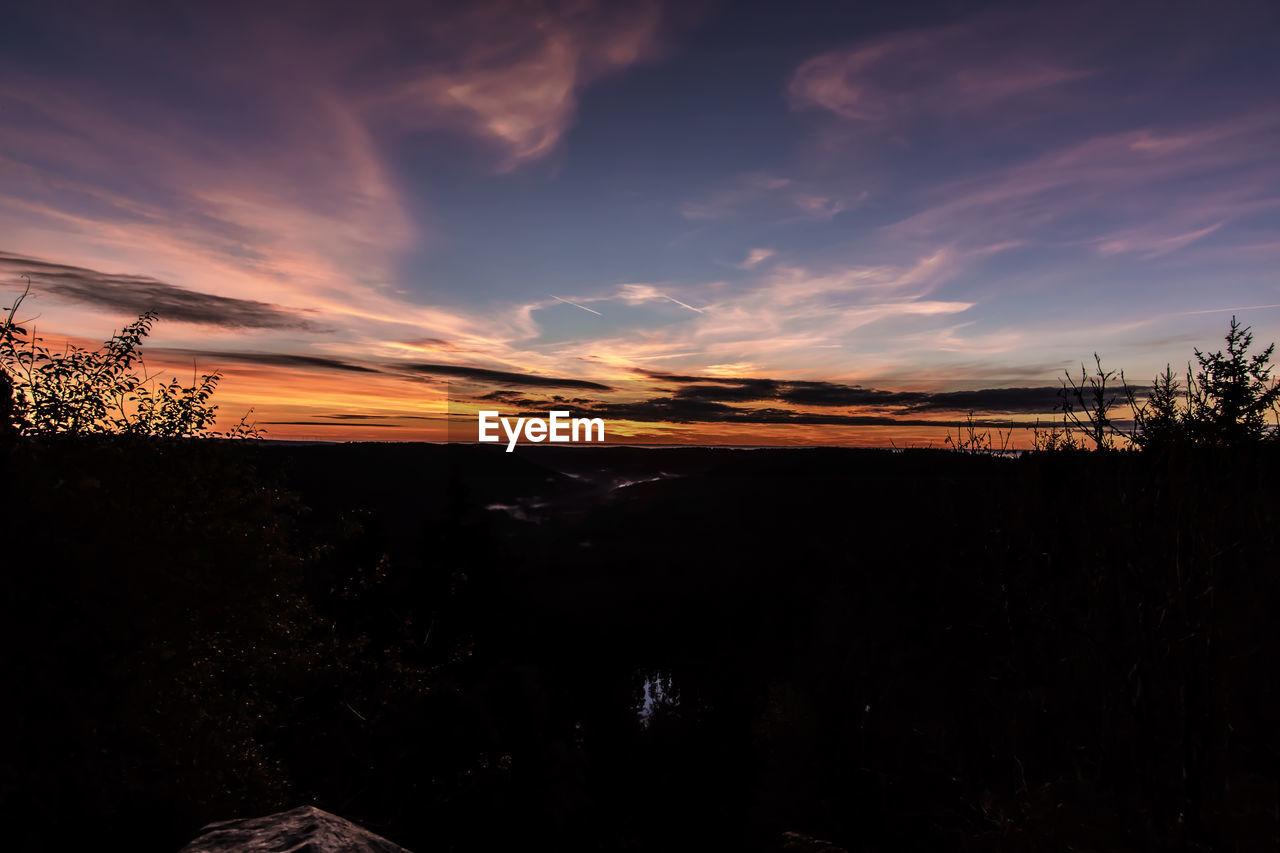 Silhouette landscape against sky at dusk