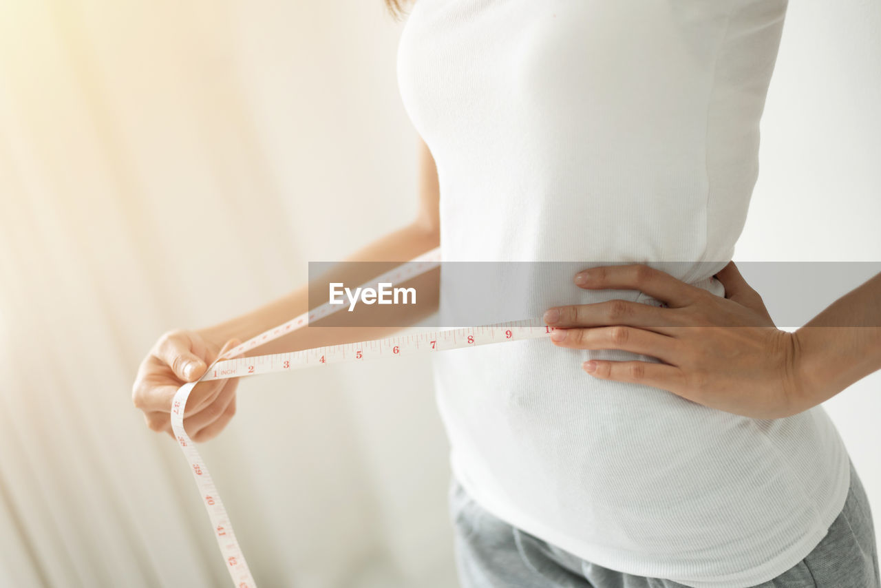 midsection, one person, hand, women, human body part, standing, indoors, adult, lifestyles, holding, human hand, tape measure, white color, human abdomen, body part, close-up, waist, focus on foreground, instrument of measurement, dieting, body conscious