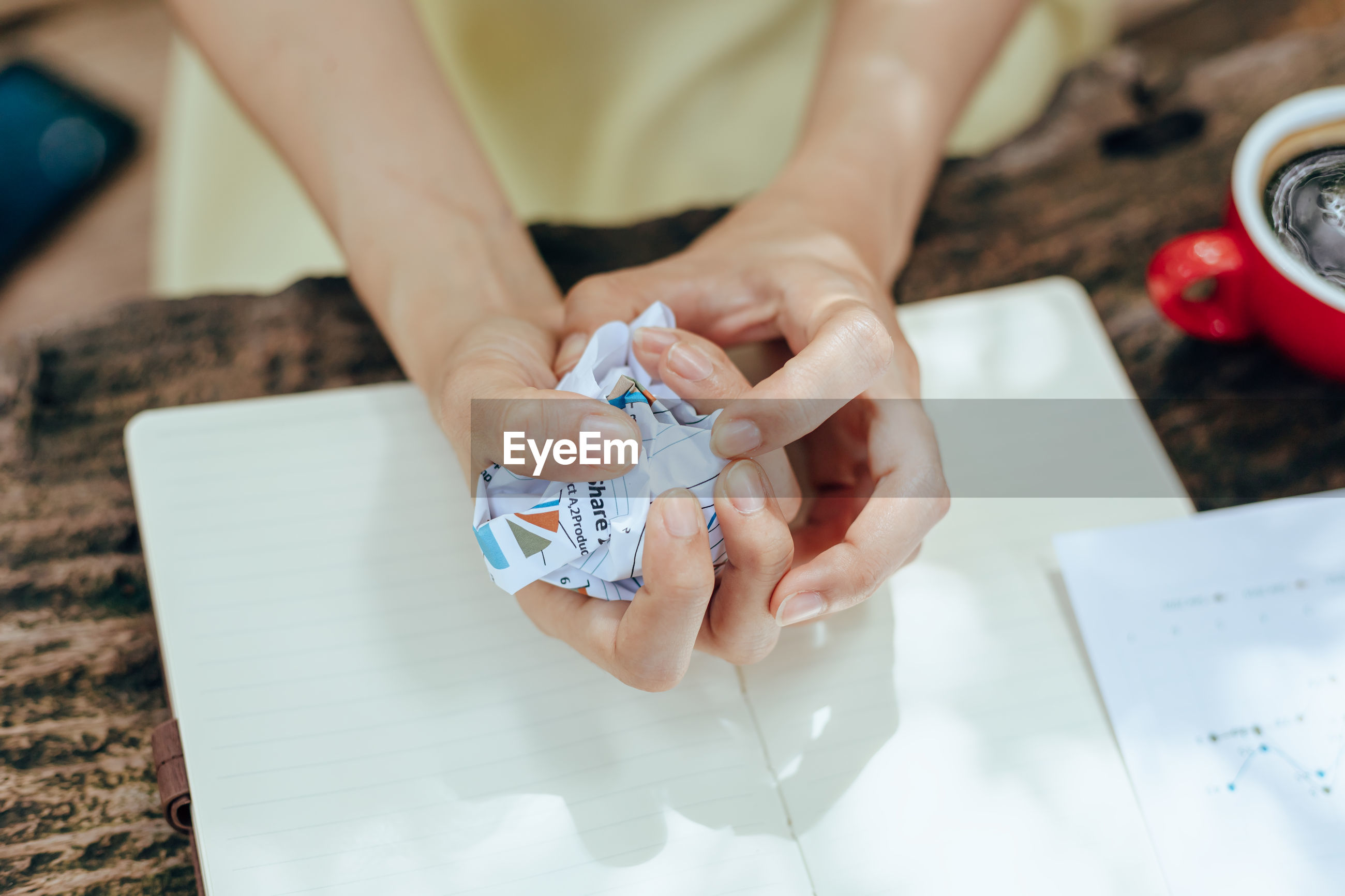 Midsection of woman holding paper with text on white table