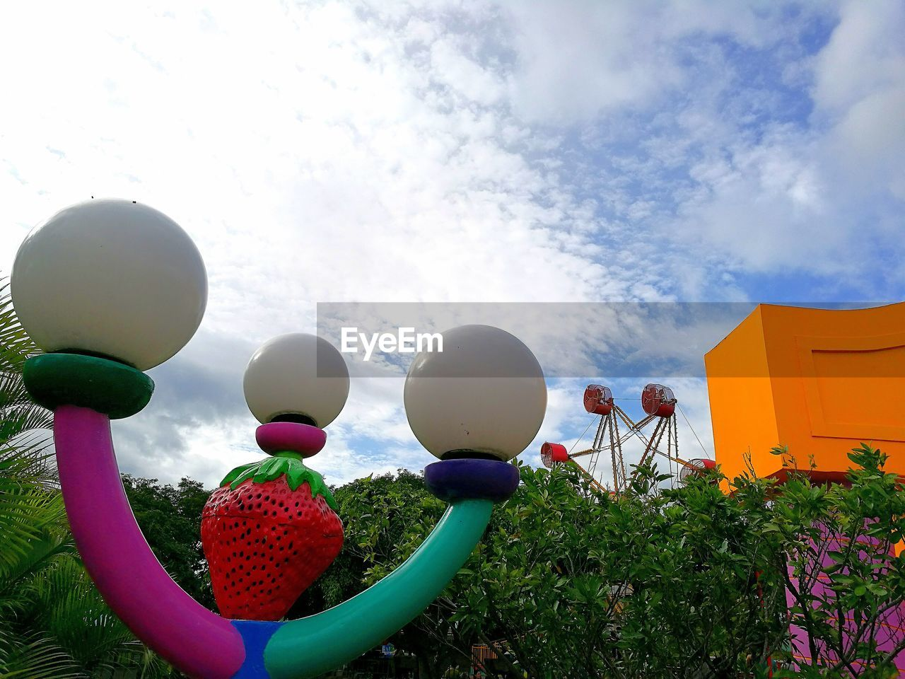 low angle view, sky, flower, multi colored, cloud - sky, balloon, outdoors, growth, day, architecture, beauty in nature, no people, building exterior, nature, fragility, freshness