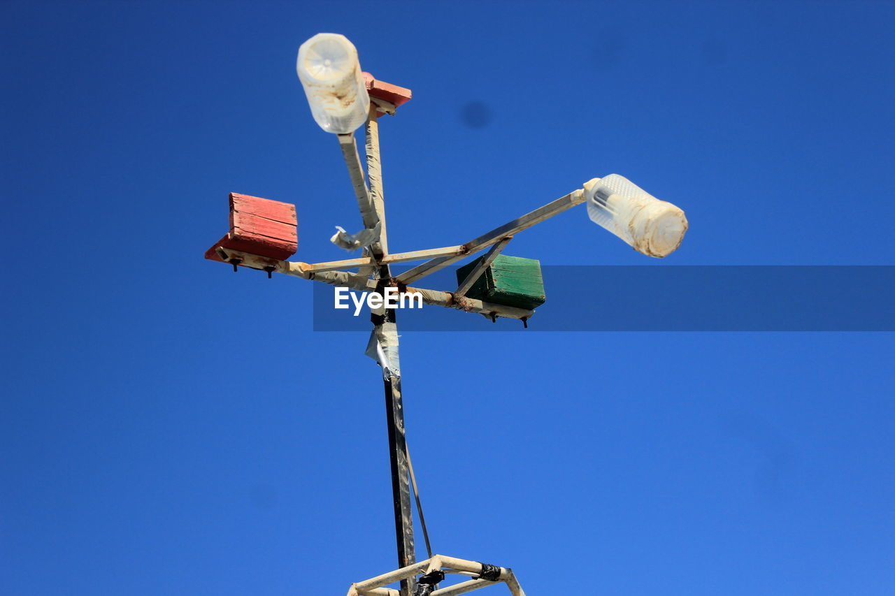low angle view, blue, sky, nature, no people, guidance, clear sky, day, lighting equipment, copy space, outdoors, sign, direction, communication, technology, symbol, metal, bird, vertebrate, arrow symbol