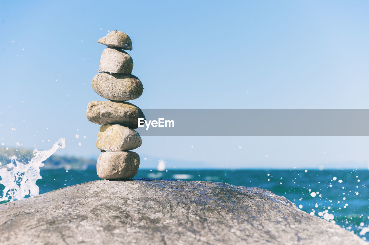 Stacked rocks by sea against clear sky