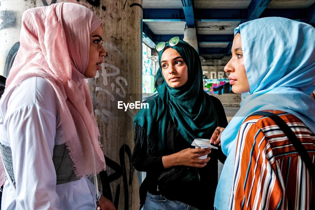 communication, group of people, clothing, real people, mobile phone, wireless technology, waist up, people, young adult, hijab, technology, indoors, hood, women, lifestyles, young women, men, telephone, headscarf, hood - clothing, teenager