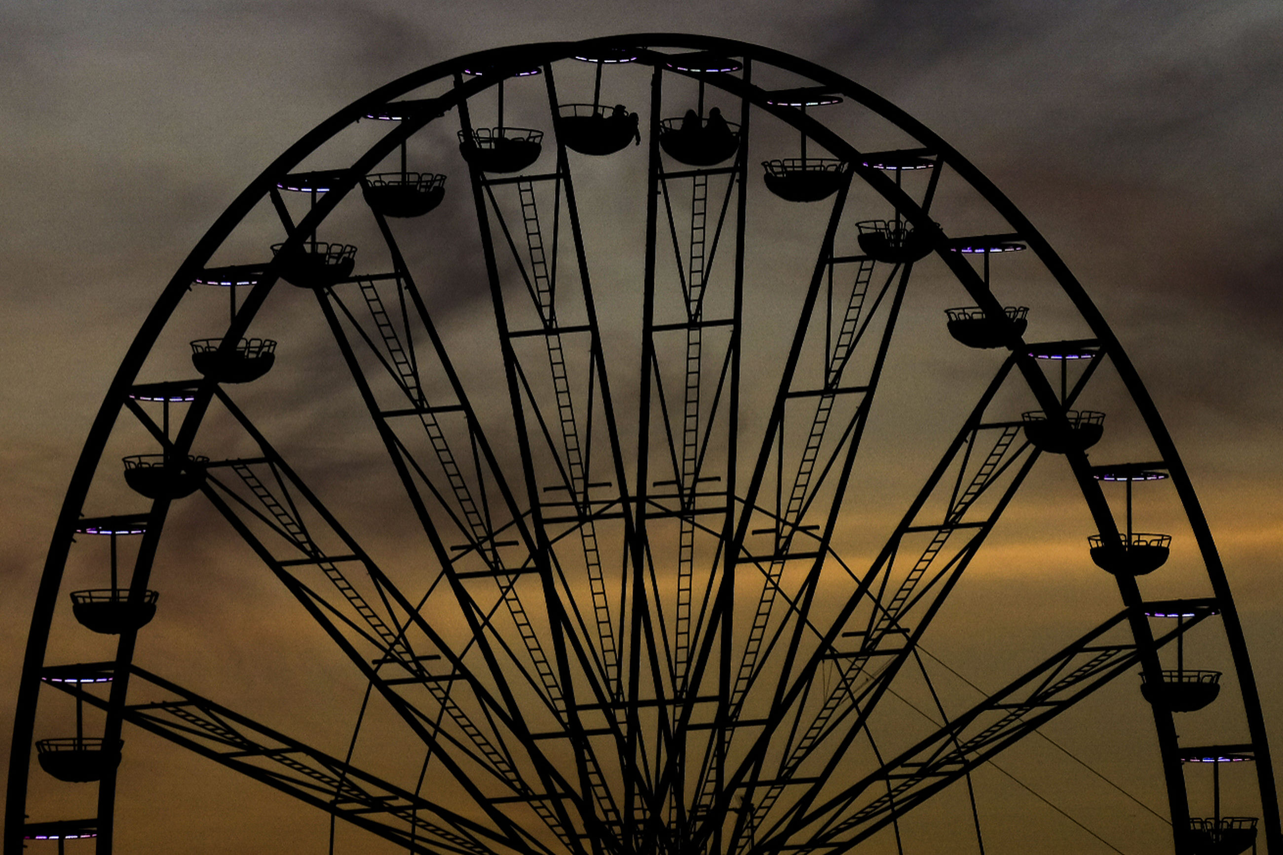 Low angle view of silhouette ferris wheel against cloudy sky during sunset