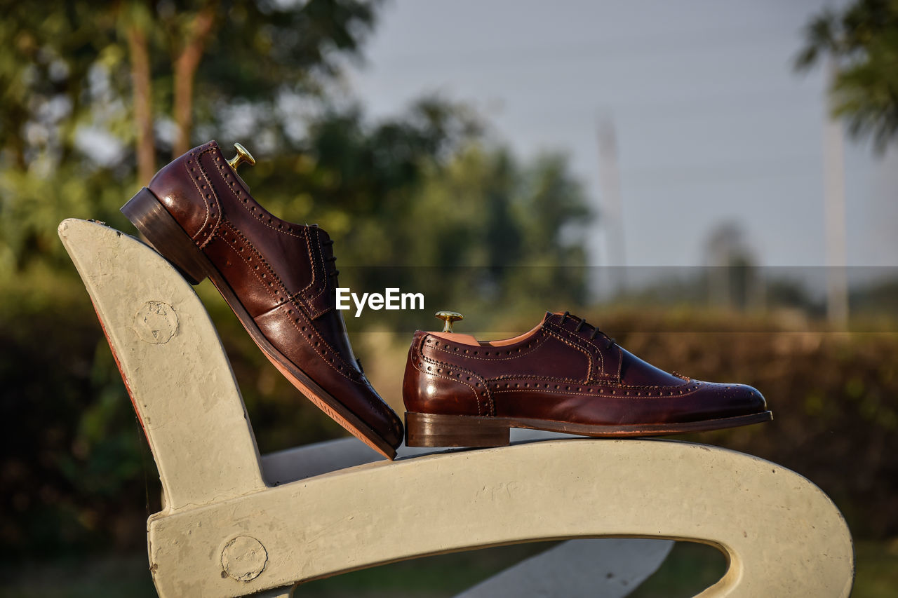 shoe, focus on foreground, day, no people, close-up, nature, metal, outdoors, plant, brown, old, tree, leather, selective focus, pair, still life, rusty, sunlight, communication, sky, personal accessory