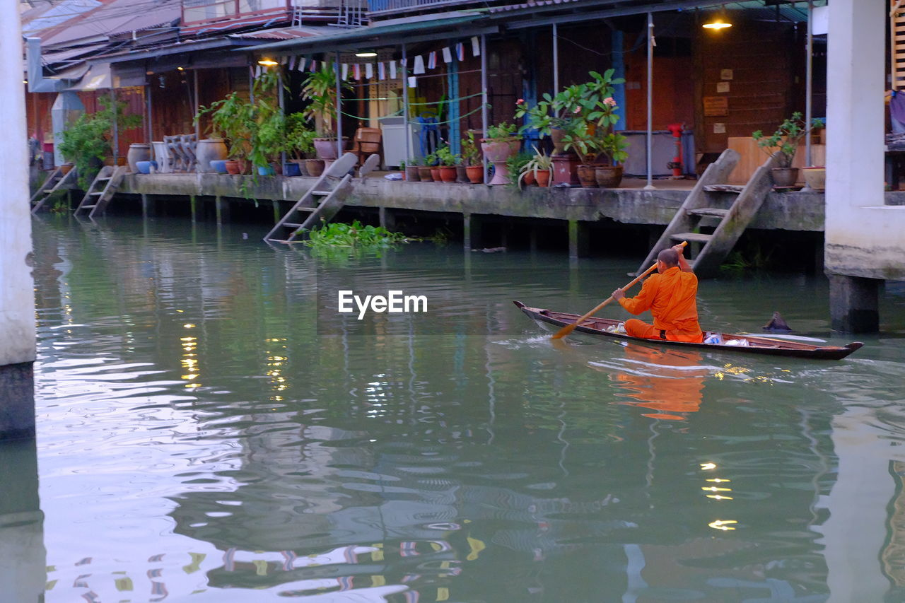 Rear view of monk boating on canal at floating market in city