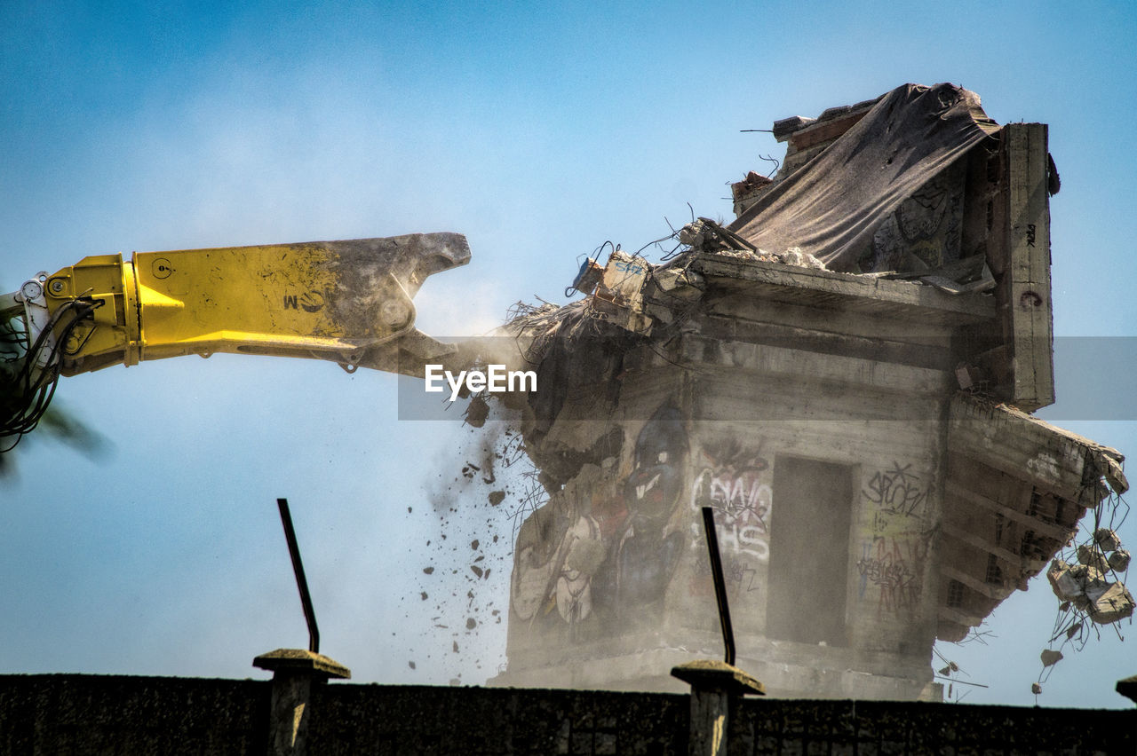 Earth mover demolishing building against clear sky