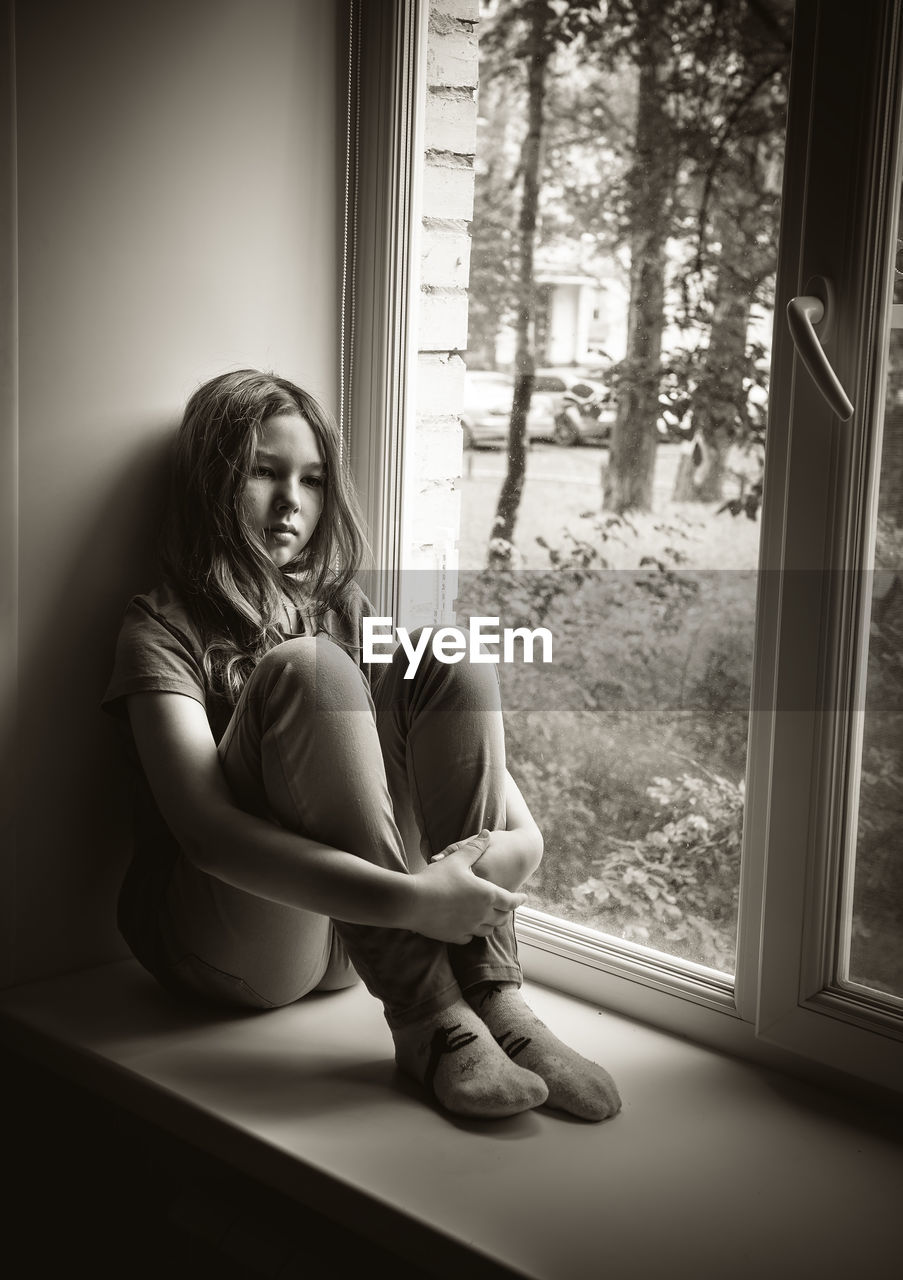 Depressed Girl Hugging Knees On Window Sill At Home