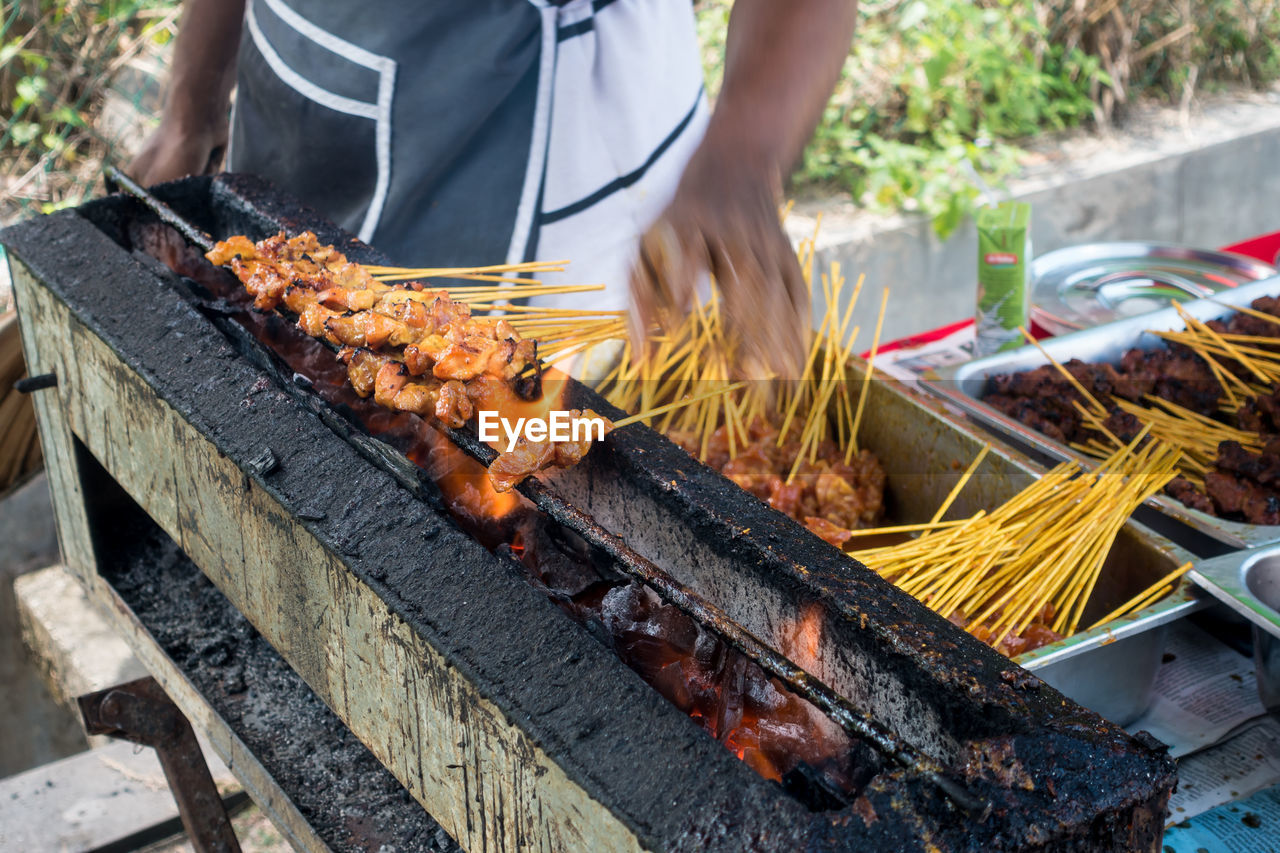 one person, barbecue, outdoors, real people, midsection, burning, food and drink, day, grilled, heat - temperature, men, food, freshness, healthy eating, apiculture, adult, people