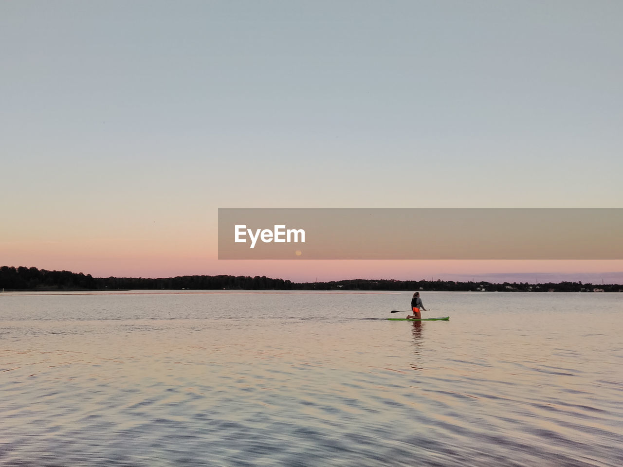 Woman Paddleboarding In Sea Against Clear Sky During Sunset