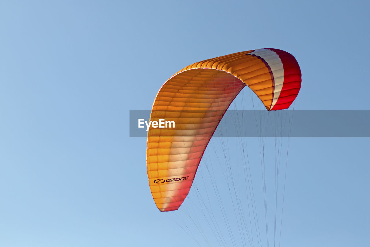 sky, extreme sports, parachute, paragliding, low angle view, mid-air, adventure, sport, flying, copy space, leisure activity, blue, nature, clear sky, transportation, gliding, freedom, joy, day, real people