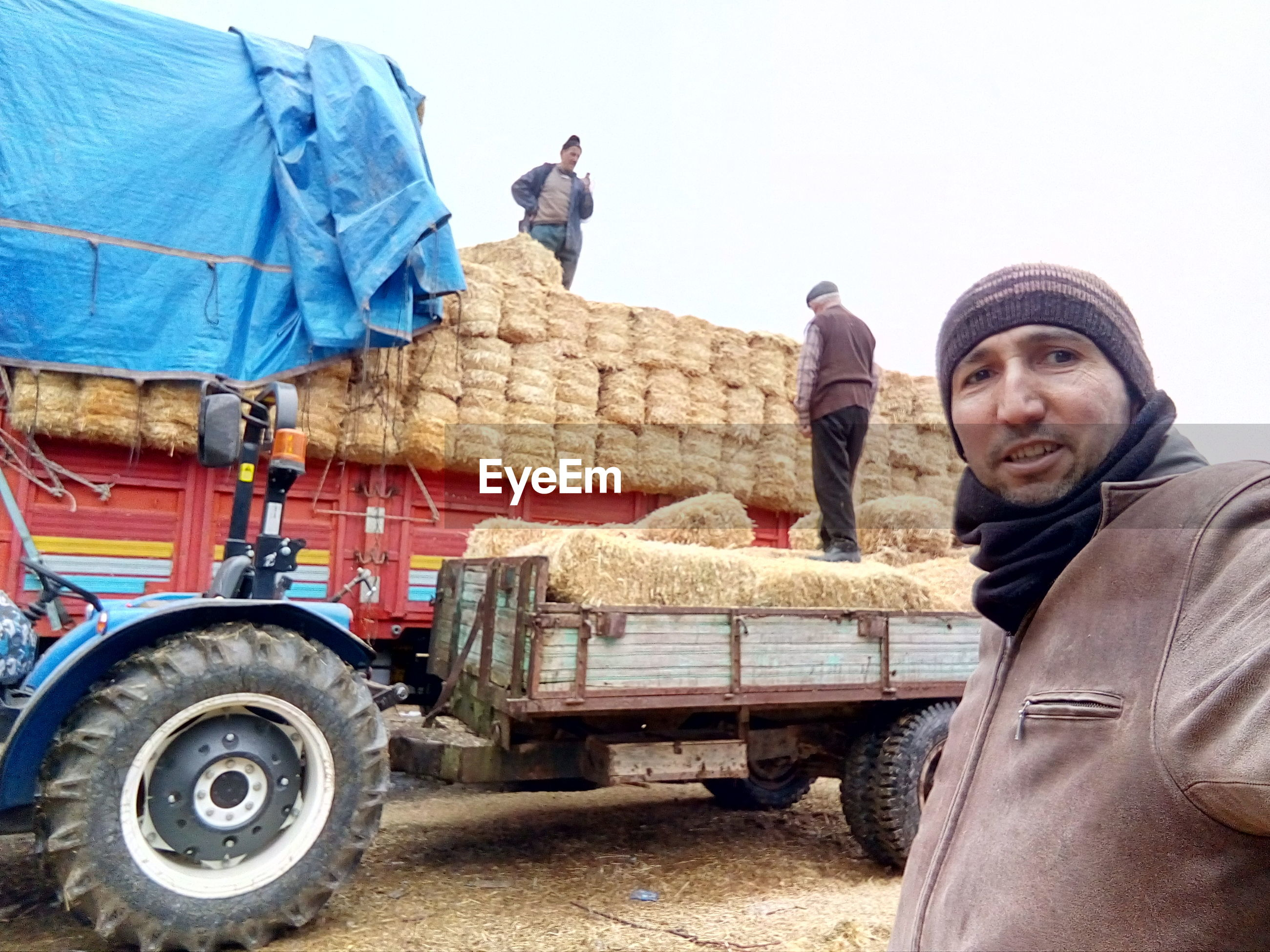 Portrait of man standing against truck at agricultural field