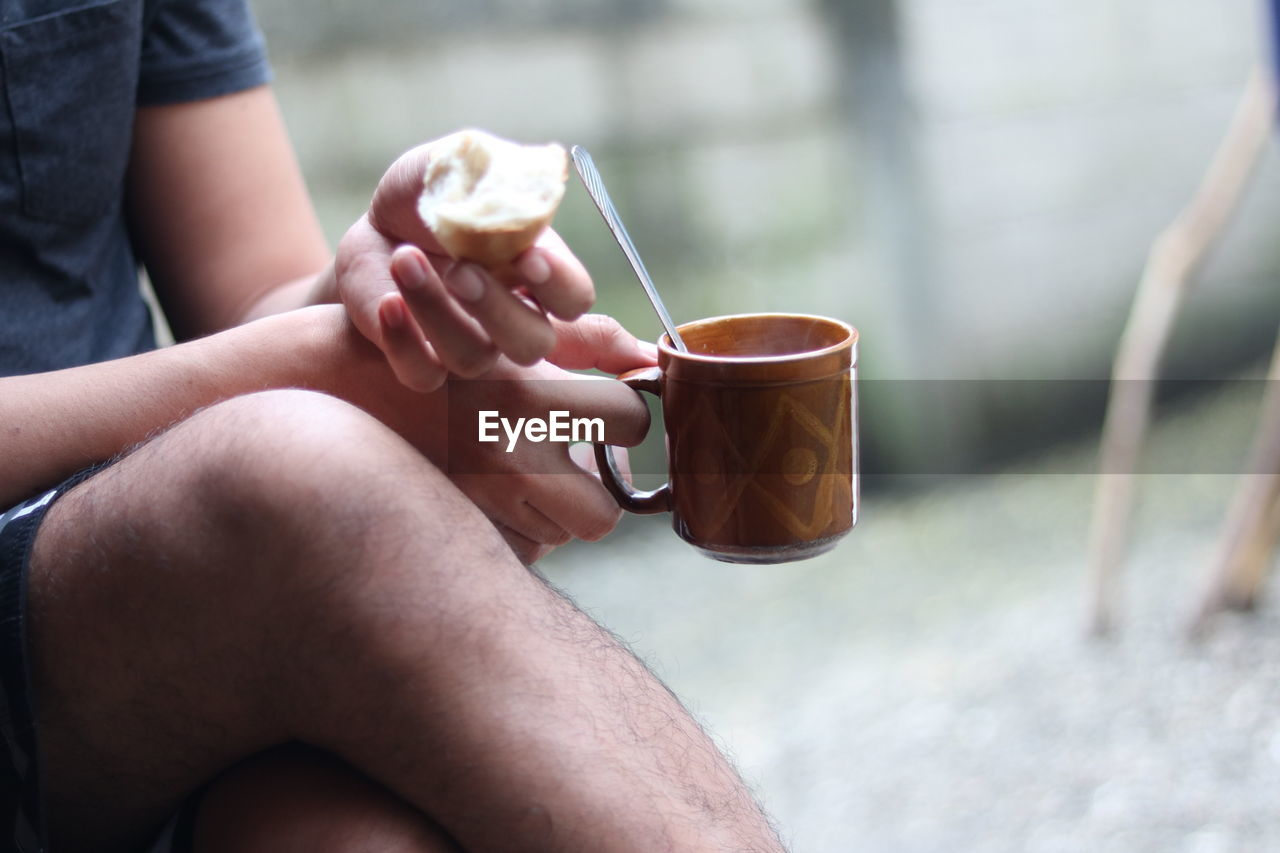 Midsection Of Man Holding Coffee Cup While Sitting Outdoors