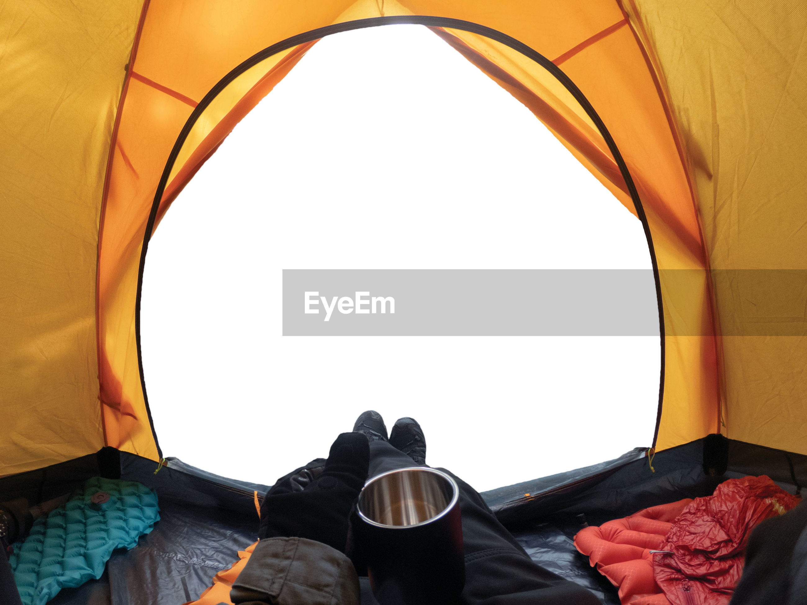 Low section of person relaxing in tent against sky