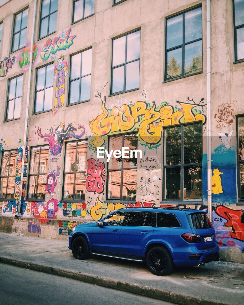 graffiti, architecture, built structure, car, building exterior, transportation, mode of transport, multi colored, land vehicle, street art, street, day, window, outdoors, no people, city