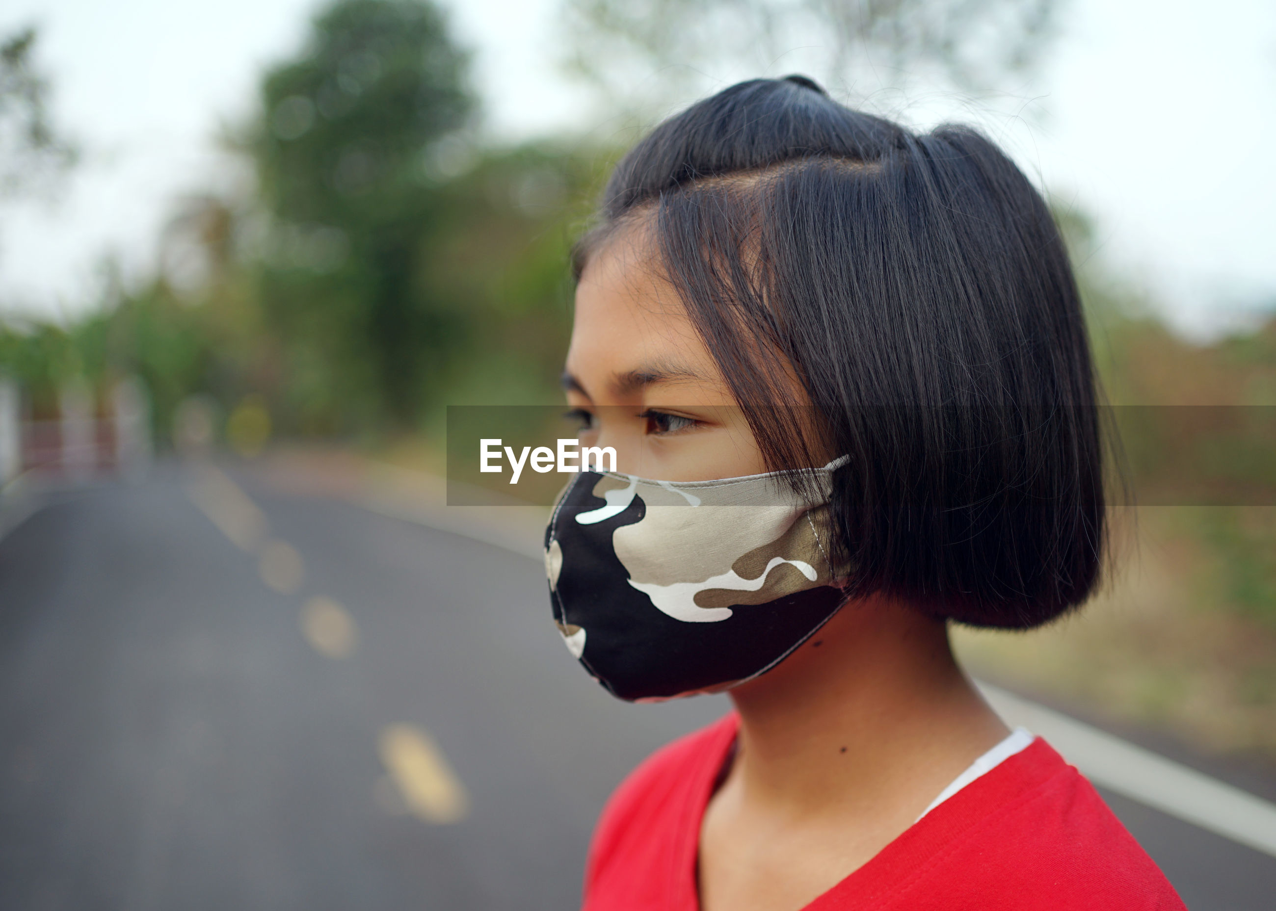 Close-up of girl wearing flu mask standing outdoors