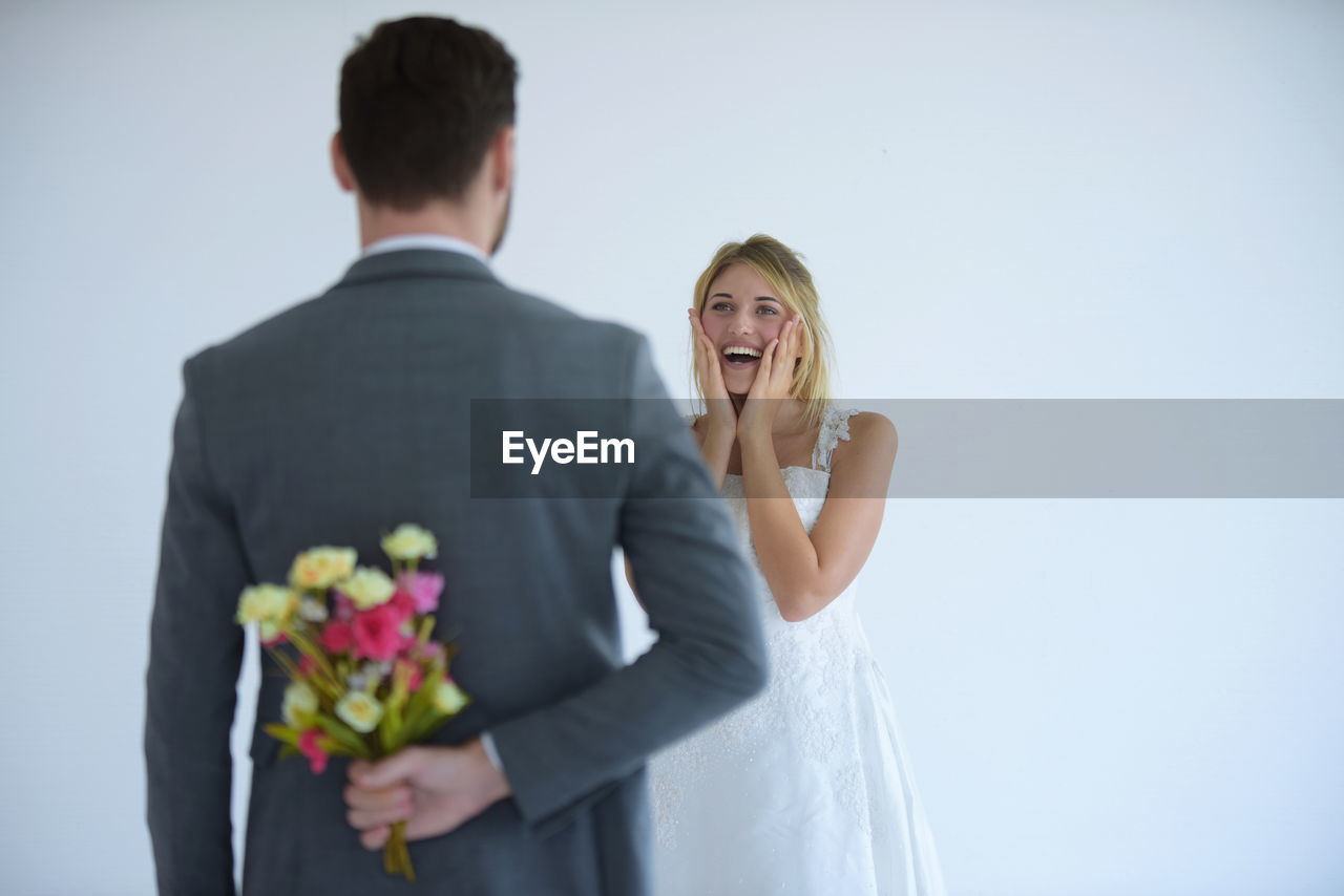 Bridegroom hiding bouquet from bride standing against white background
