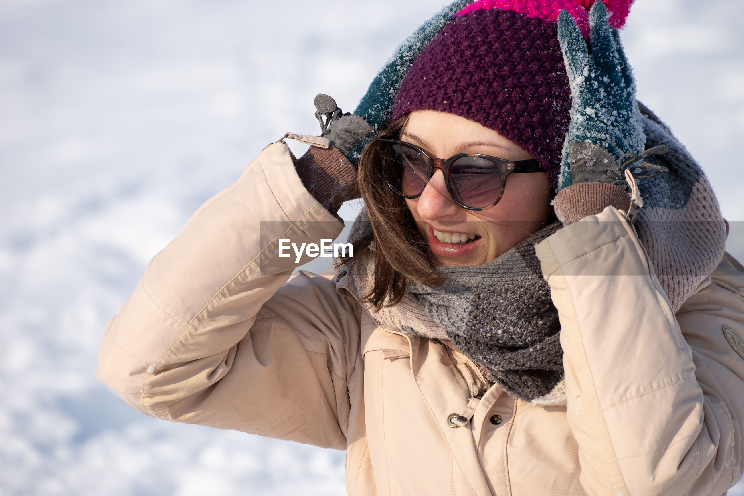Smiling woman wearing sunglasses standing outdoors during winter