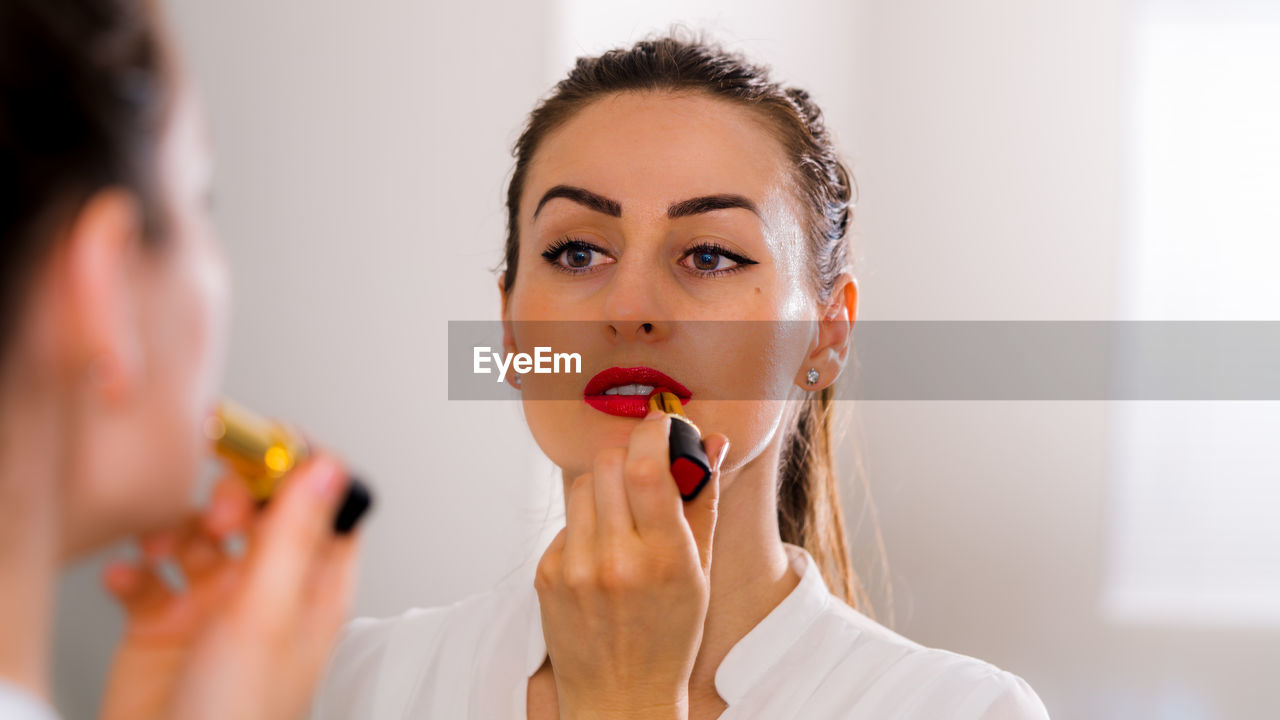 Close-up of beautiful woman wearing lipstick while standing in front of mirror