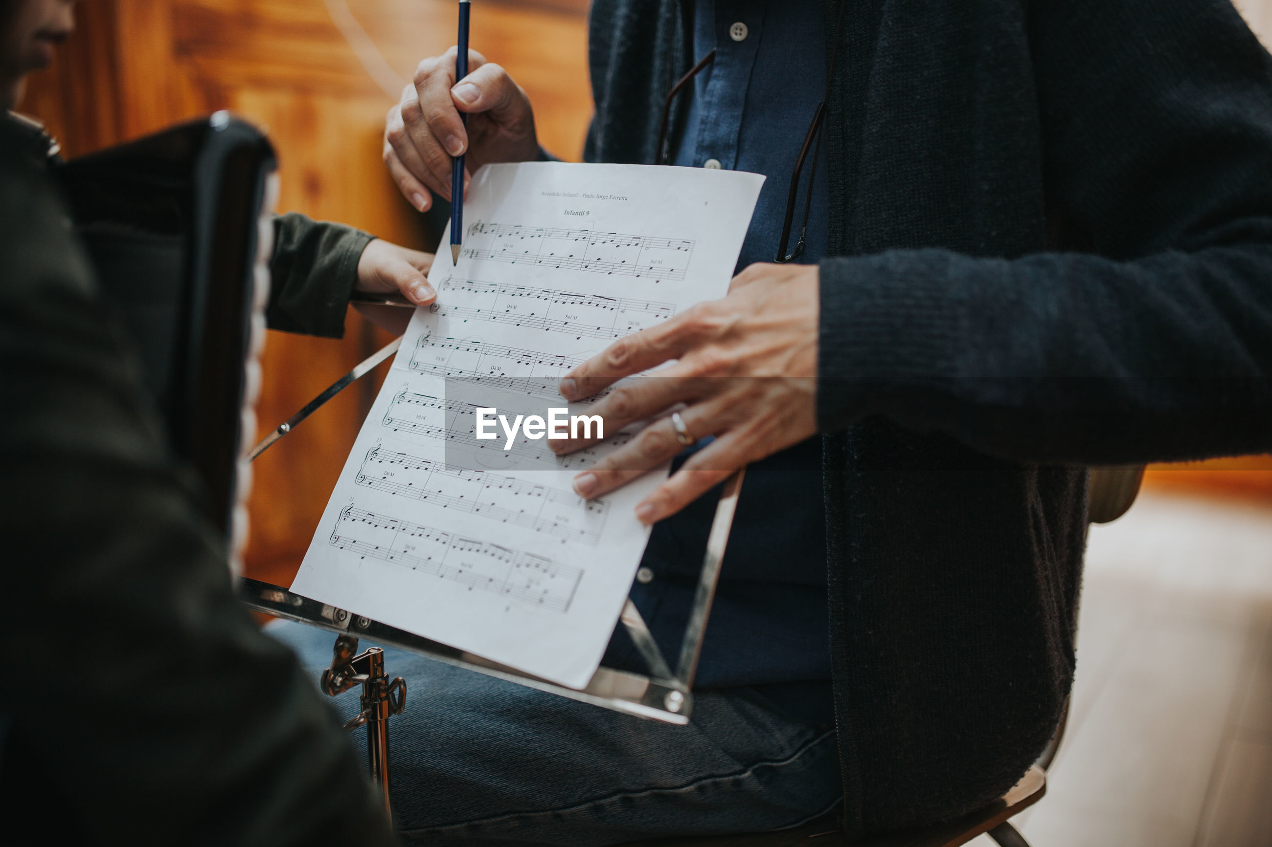 Midsection of man teaching music to student