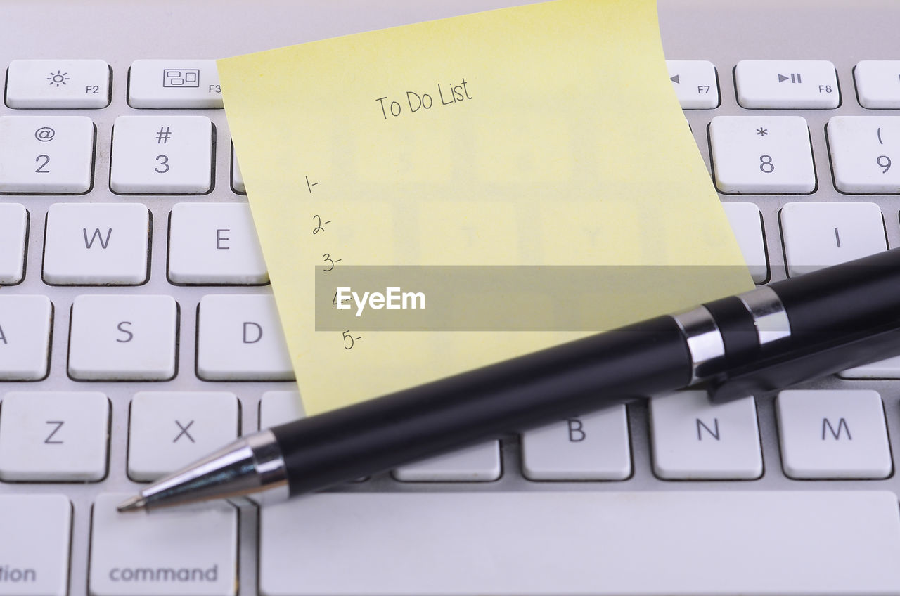 Close-up of pen with adhesive note on computer keyboard