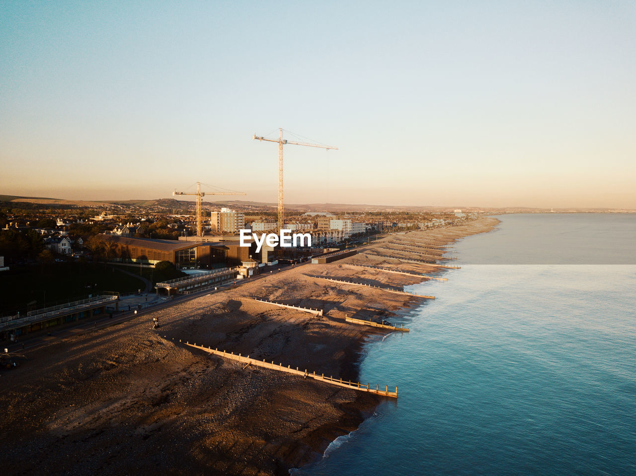 sky, water, architecture, nature, built structure, sea, sunset, clear sky, building exterior, no people, outdoors, industry, high angle view, tranquil scene, copy space, scenics - nature, day, horizon, fuel and power generation, construction equipment