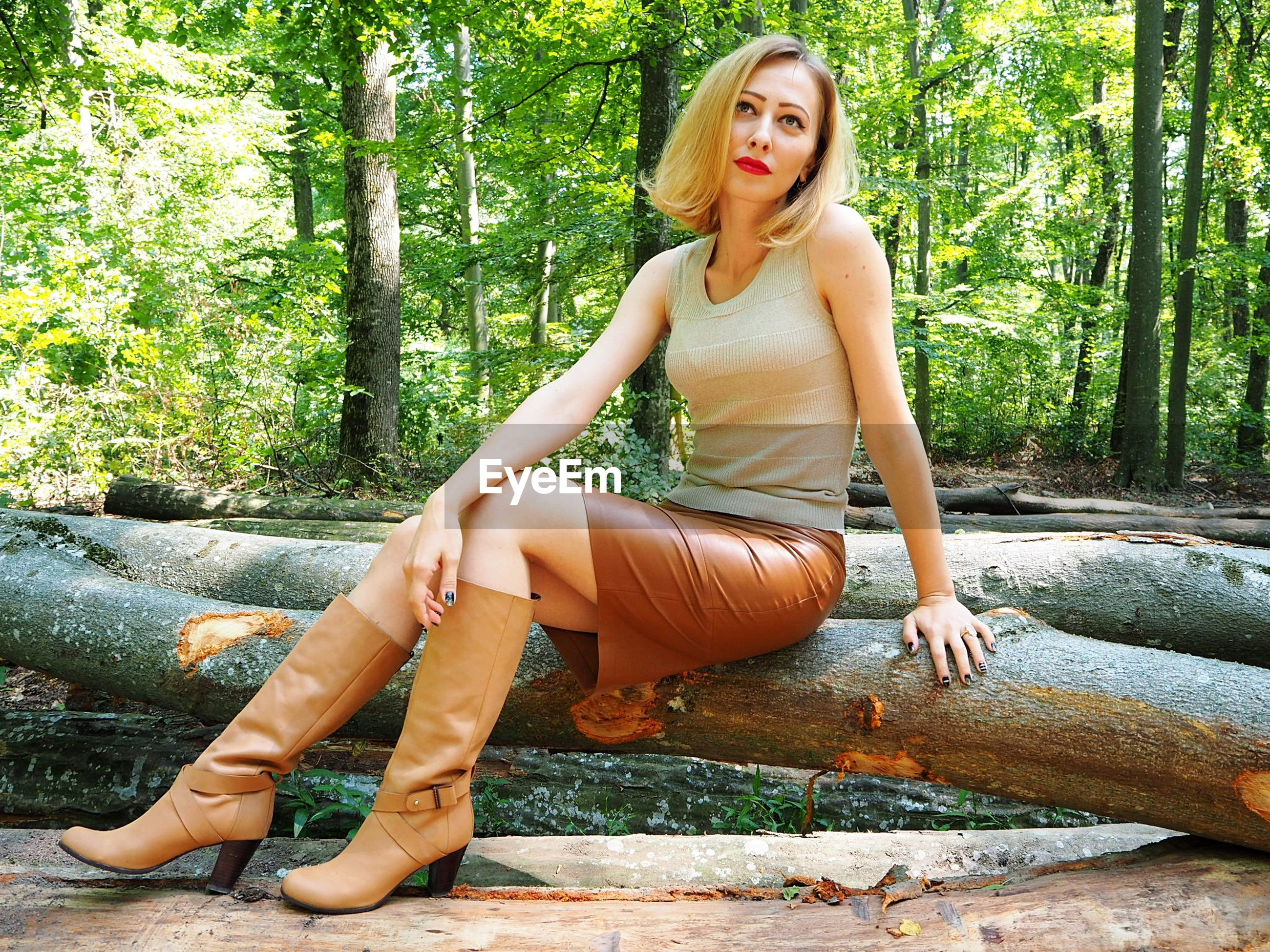 Thoughtful woman sitting on fallen tree at forest