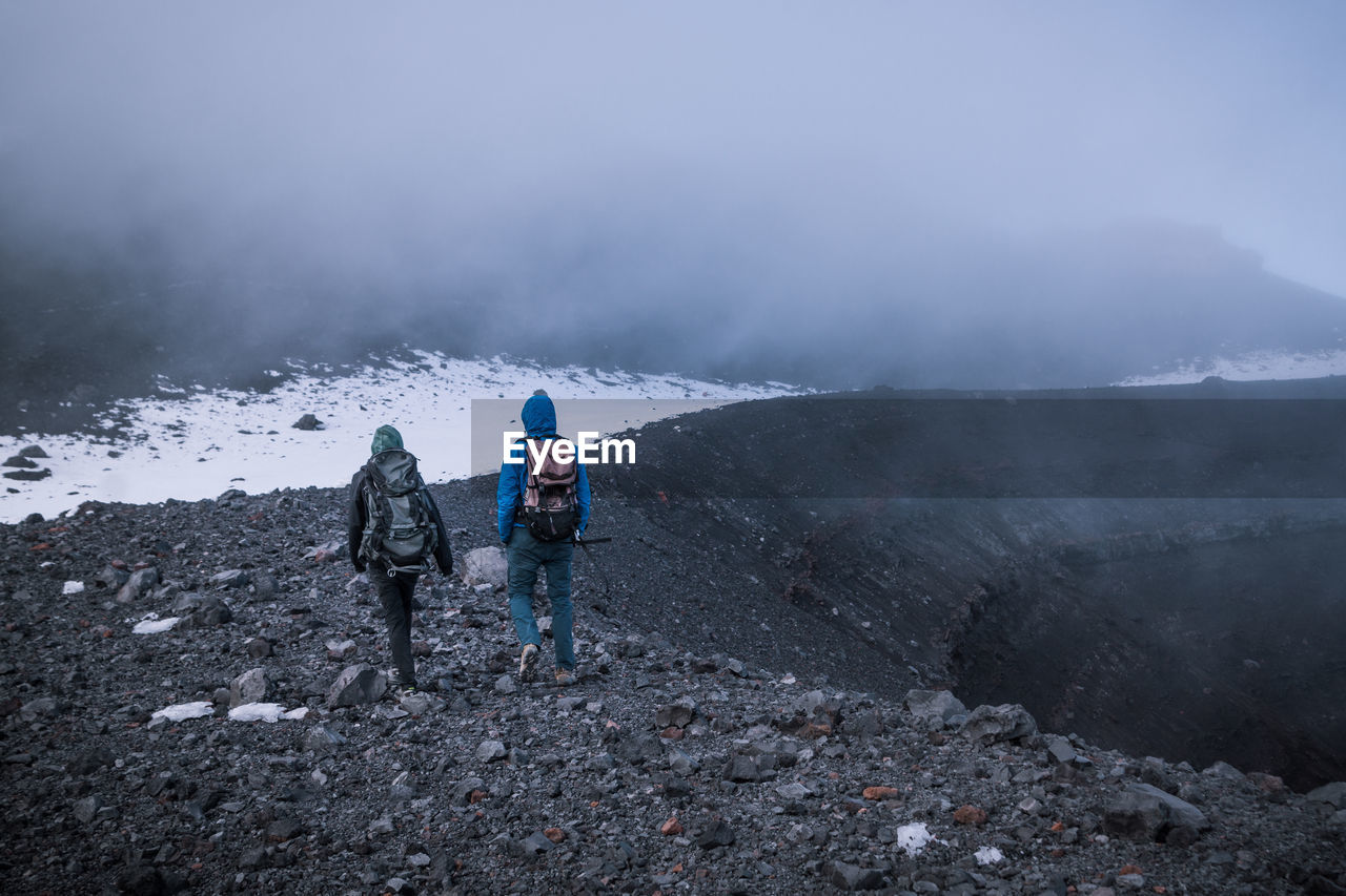 Rear View Of Male Hikers Hiking On Mountain During Winter