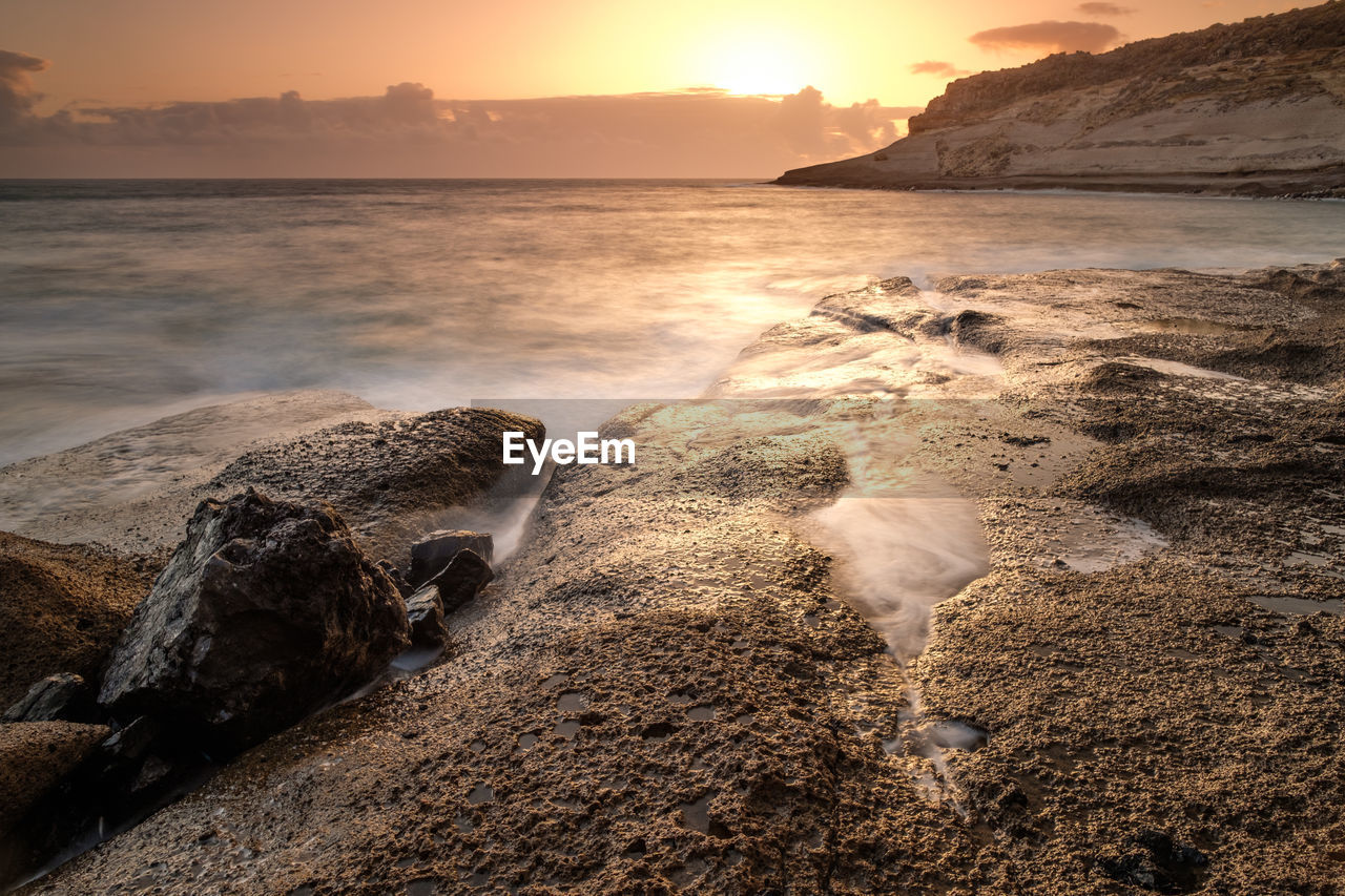 sea, water, beach, beauty in nature, sky, land, sunset, scenics - nature, nature, rock, no people, tranquility, solid, motion, tranquil scene, rock - object, horizon, idyllic, horizon over water, outdoors, rocky coastline