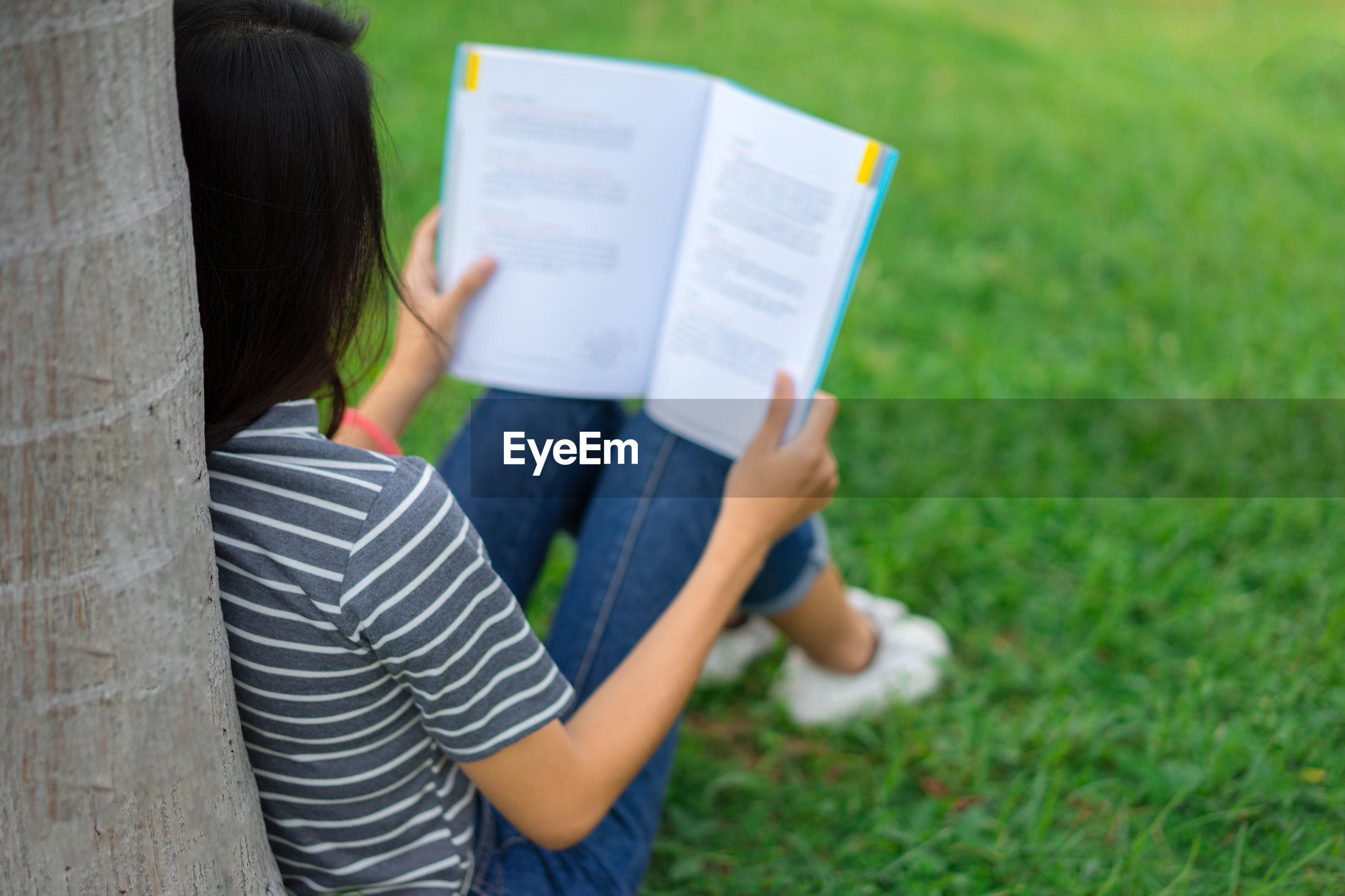 Young woman reading book while sitting on field