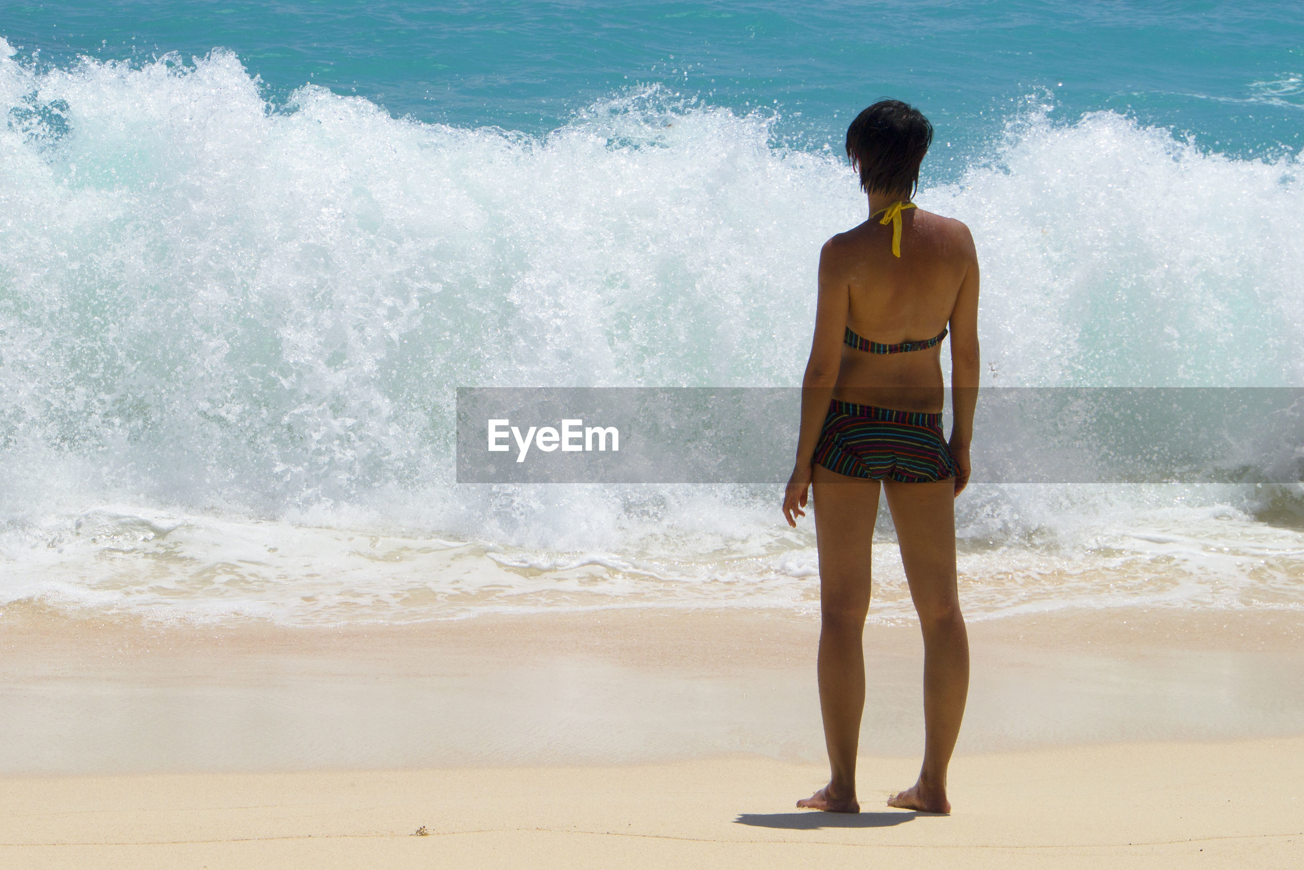 Rear view of woman standing against waves in sea