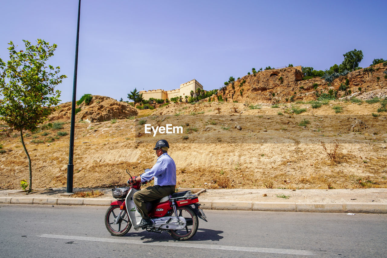 transportation, real people, one person, mode of transportation, road, land vehicle, sky, full length, lifestyles, nature, casual clothing, day, riding, sunlight, ride, men, sitting, leisure activity, adult, outdoors