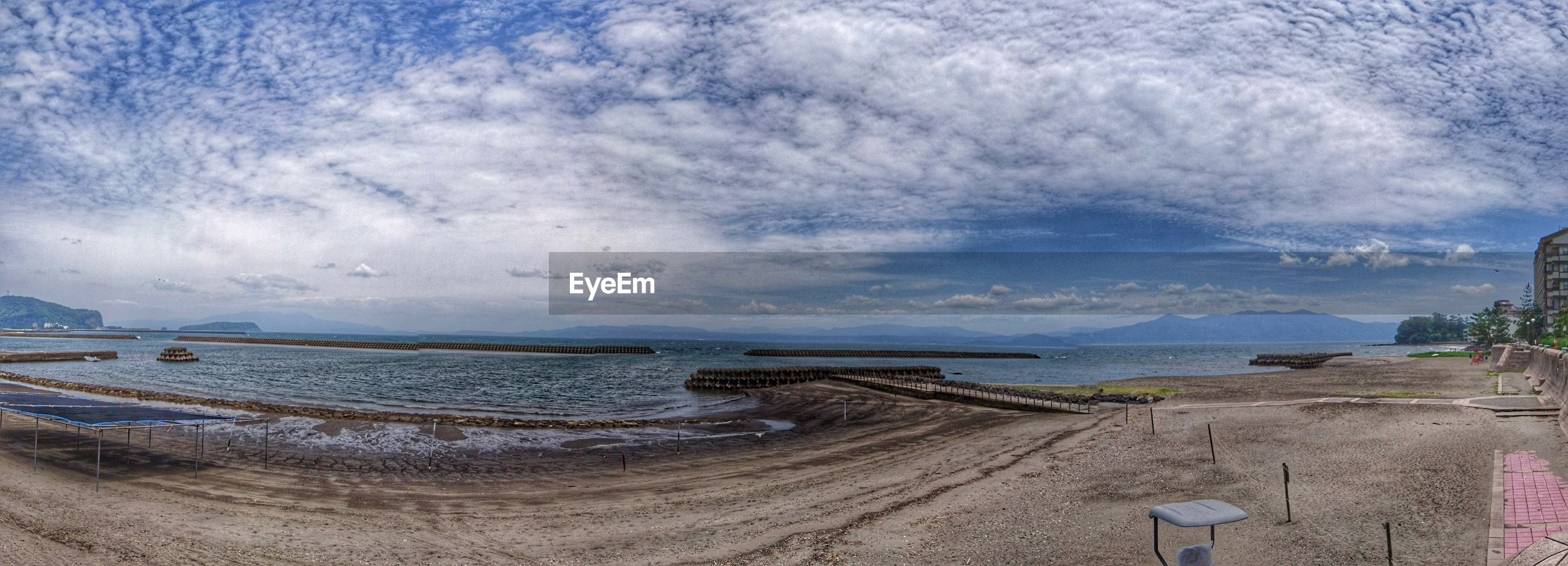 PANORAMIC SHOT OF CALM SEA AGAINST CLOUDY SKY