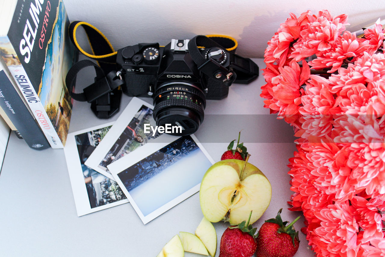HIGH ANGLE VIEW OF VARIOUS FLOWER ON TABLE AGAINST WALL