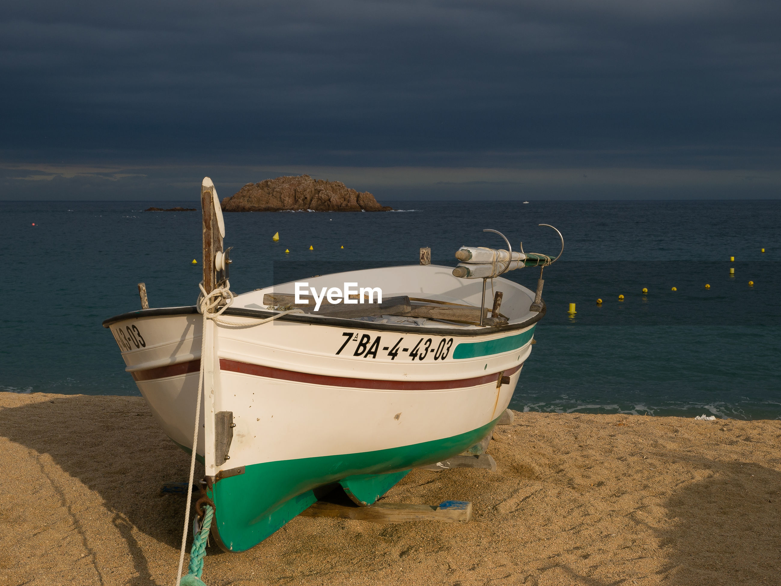 Boat moored on beach against cloudy sky