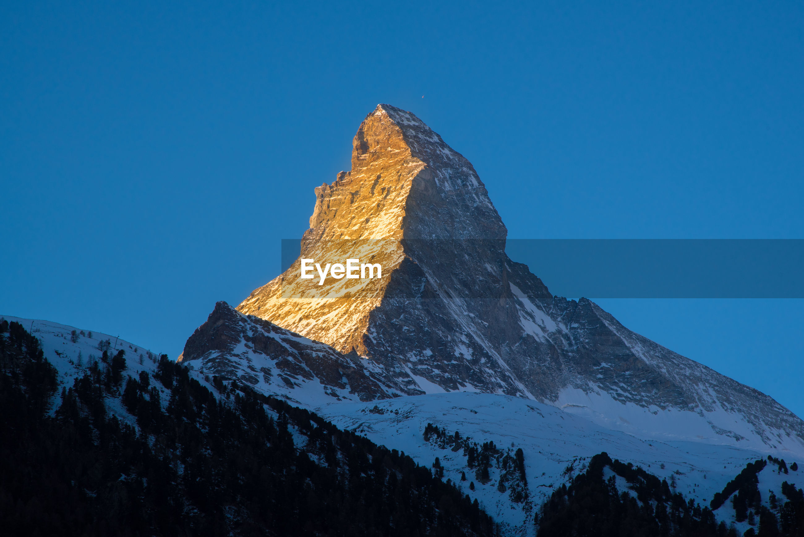 Low angle view of snowcapped mountain against clear blue sky during sunset