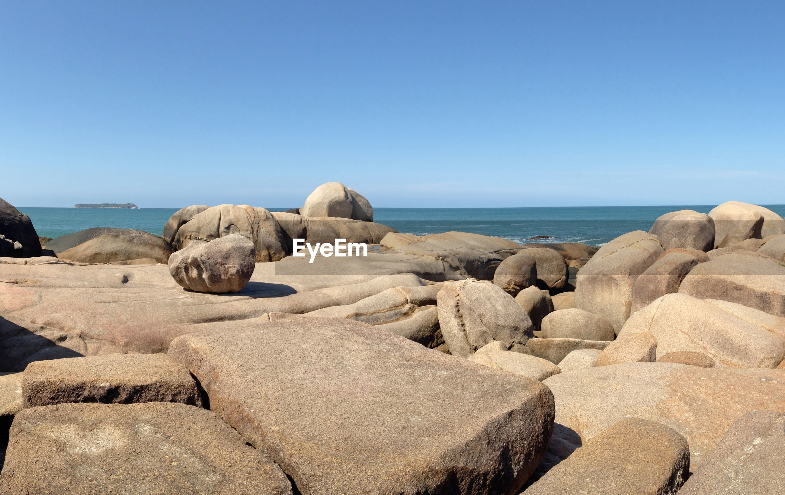 ROCKS ON SEA SHORE AGAINST CLEAR BLUE SKY