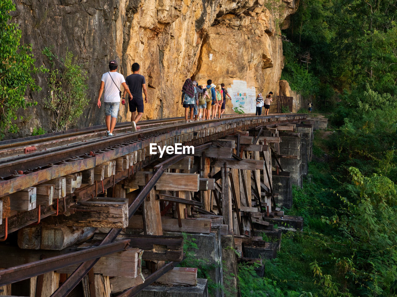 People walking on railroad tracks by mountain
