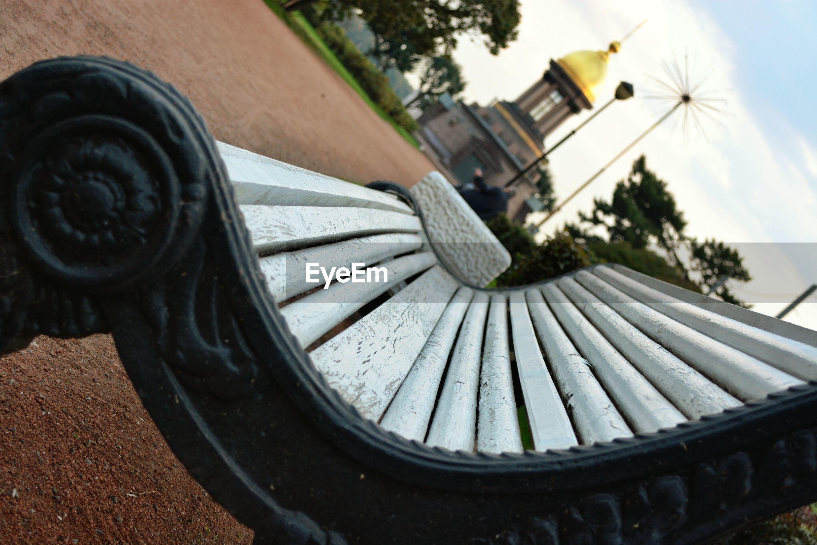Tilt image of bench against sky in park