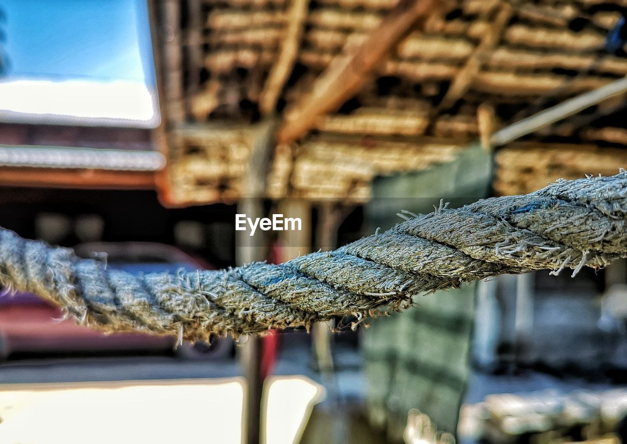 rope, strength, focus on foreground, no people, close-up, day, pattern, connection, architecture, outdoors, metal, tied up, nature, selective focus, built structure, wood - material, transportation, sunlight, twisted, textured