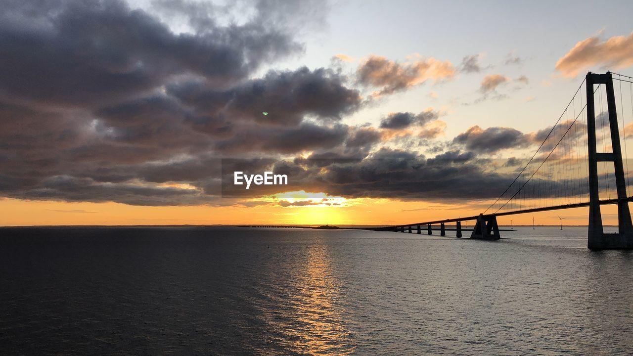Silhouette bridge over sea against sky during sunset
