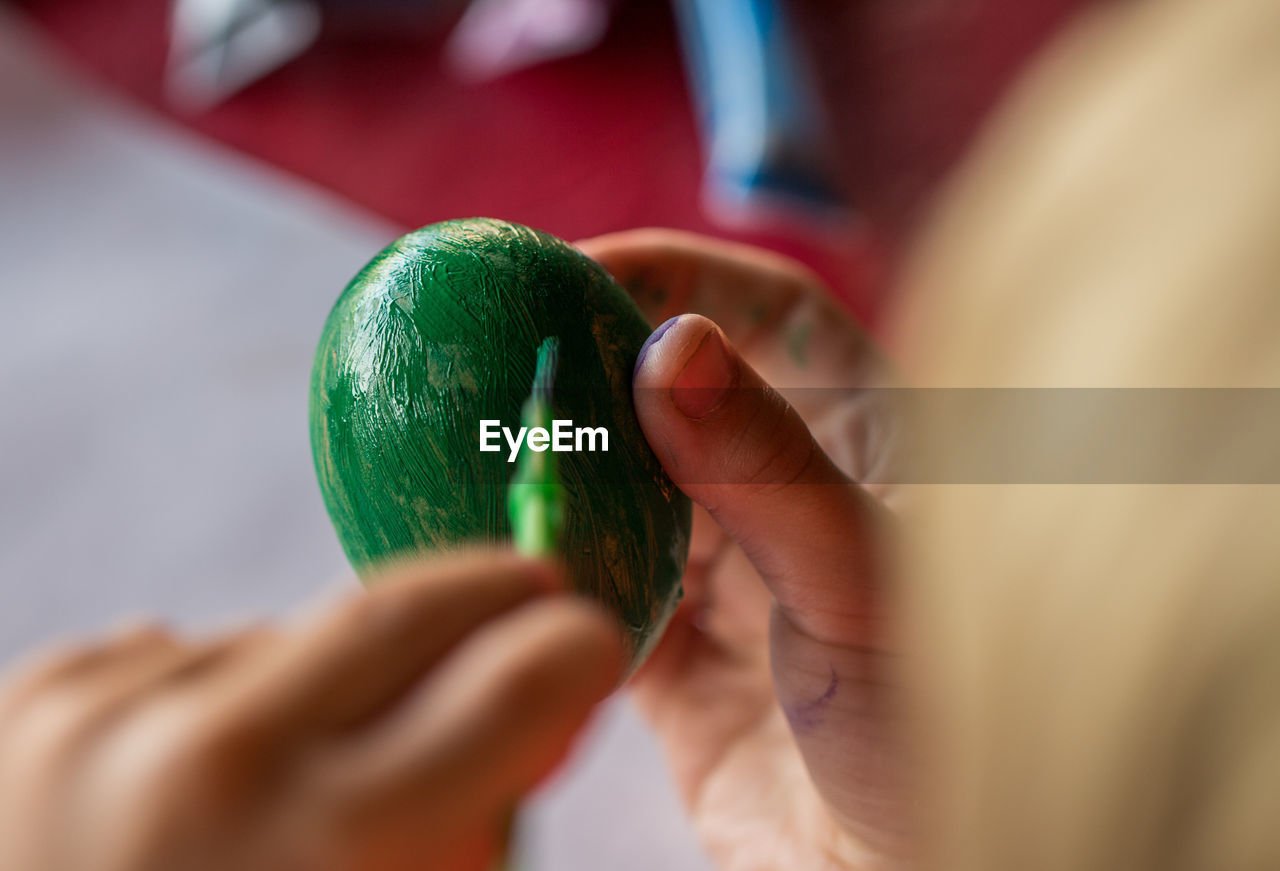 Close-Up Of Woman Painting Easter Egg