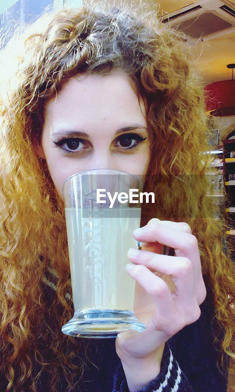 looking at camera, drink, drinking, portrait, drinking glass, curly hair, refreshment, one person, real people, indoors, young adult, close-up, young women, beautiful woman, day, people