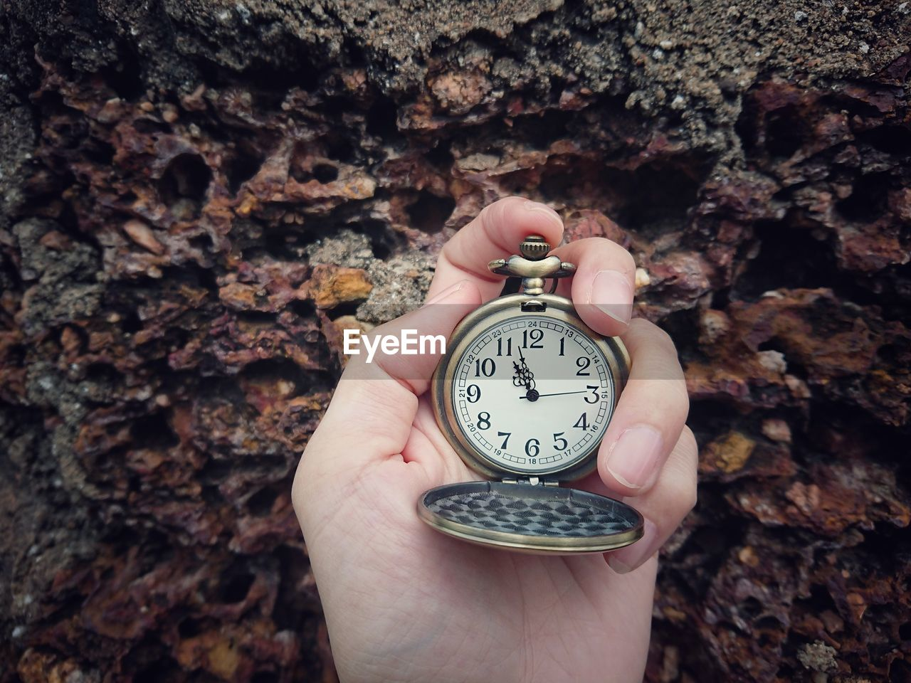 Cropped hand holding pocket watch